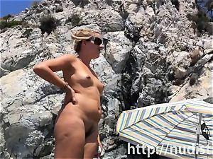 Spy webcam shot of a warm nudist honey tanning on the beach